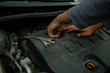 A hand technician checking or fixing the engine of a modern car. mechanic performing maintenance and car maintenance. charge the battery in the cold