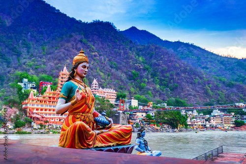 Idol indyjskiego boga / bogini lub bóstwa, nad brzegiem rzeki Ganga w Rishikesh z niewyraźną świątynią w tle, stolicą jogi Indii. Turystyka indyjska