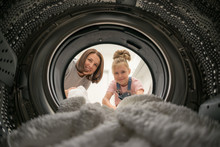Woman Doing Laundry With Her D...