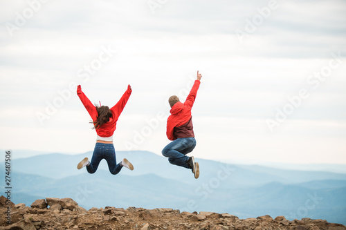 Young happy couple jumping in the background of the mountain Canvas Print