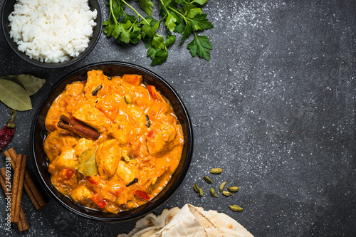 Photo  Chicken tikka masala with rice on black top view.