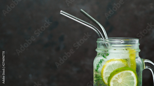 Gris traffic Cold drink in mason jar with metal straw on black background. Lemonade or detox water with lime and thyme in glass jar with copy space for text or design. Recyclable straws, zero waste concept. Banner
