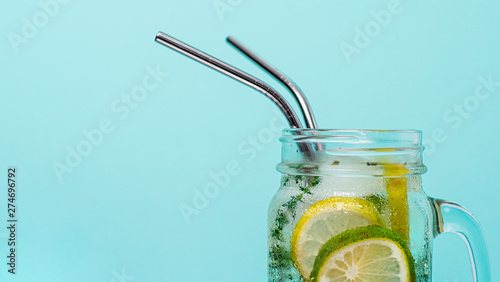 Fototapeta Cold drink in mason jar with metal straw on blue background