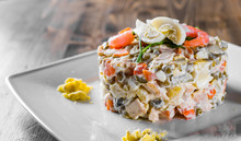 Olivier Salad With Shrimps, Eggs And Vegetables In A Plate On Wooden Table