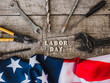 LABOR DAY. Hand tools, American Flag and wooden letters lying on the desk. Top view, close-up. Congratulations to family, relatives, friends, colleagues. Concept of labor and employment