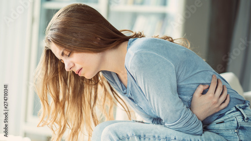 Fotografia  Unhealthy young woman with stomachache