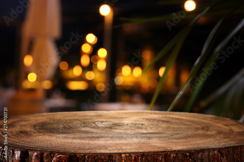 Fototapeta background of wooden table in front of abstract blurred restaurant lights obraz