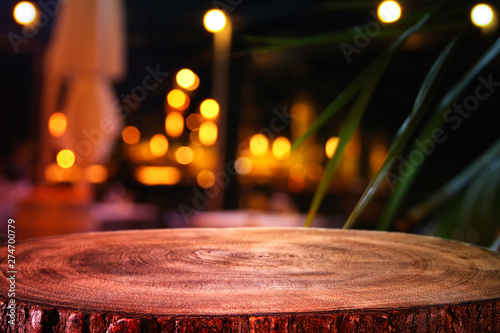 Fototapeta background of wooden table in front of abstract blurred restaurant lights obraz na płótnie