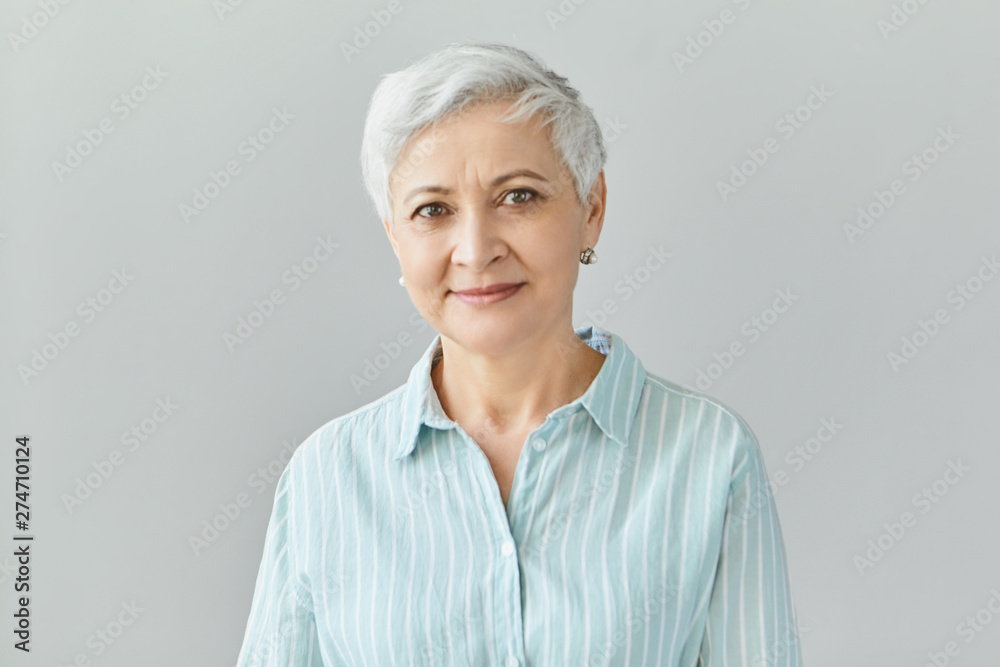 Fototapety, obrazy: Isolated image of friendly good looking European businesswoman with pixie gray hair smiling confidently at camera, glad with work results of her team, posing in studio, dressed in formal striped shirt