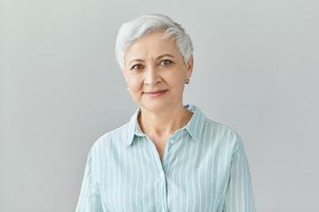 Isolated image of friendly good looking European businesswoman with pixie gray hair smiling confidently at camera, glad with work results of her team, posing in studio, dressed in formal striped shirt