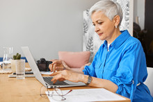 People, Job, Occupation, Age And Employment. Indoor Image Of Beautiful Gray Haired Female On Retirement Looking For Remote Work Using Portable Computer. Mature Woman Photographer Typing On Laptop