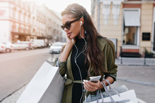 Spectacular Latin Woman In Stylish Sunglasses Chilling In City And Listening Music In Earphones. Outdoor Portrait Of Lovely Brunette Girl Holding Smartphone And Shop Bags.