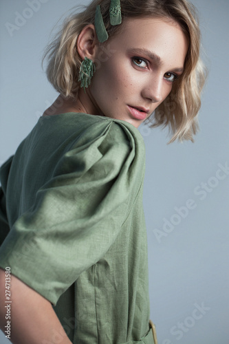 Fashion portrait of blonde female model on grey background. stylish green clothes and accessories. concept of garmonical style and atmosphere