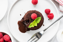 Chocolate Lava Cake On Plate With Fresh Raspberries And Mint Leaf. Top View