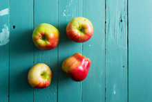 Four Apples On Blue Wooden Bac...