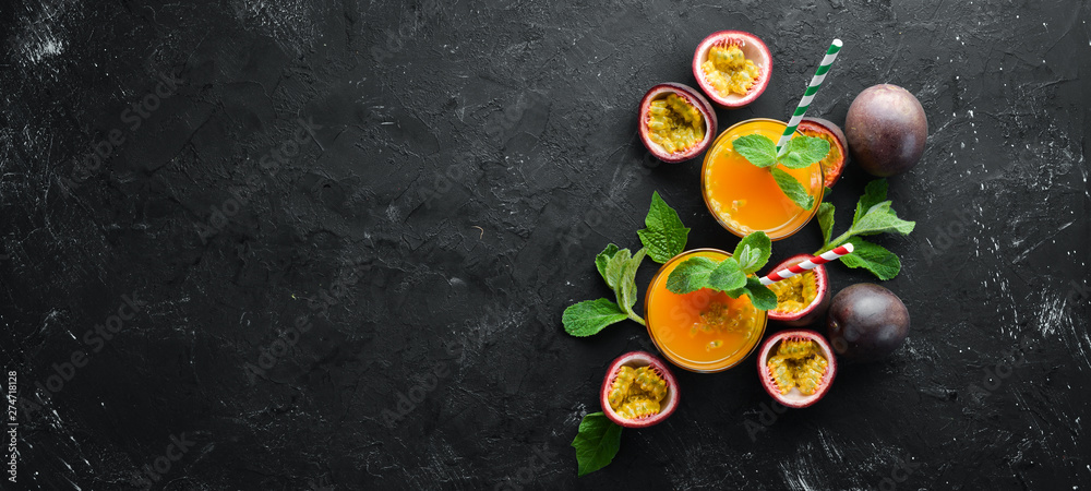 Fototapeta Passion fruits juice and fruit on a black background. Tropical Fruits. Top view. Free space for text.