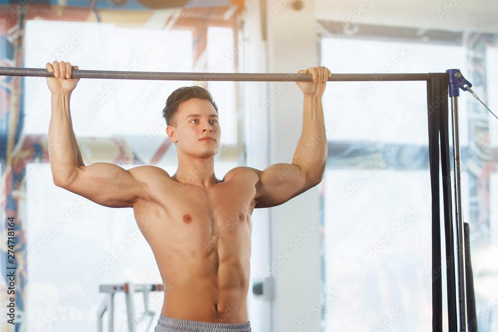 Fototapety, obrazy: Man making exercises on crossbar.