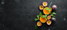 Passion Fruits Juice And Fruit On A Black Background. Tropical Fruits. Top View. Free Space For Text.