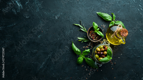 Olive oil, olives and spices on a black stone background Fototapet