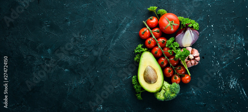 Poster Cuisine Fresh vegetables on a black background. Avocados, tomatoes, garlic, parsley, paprika. Top view. Free space for your text.
