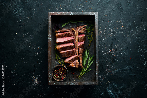 Foto op Plexiglas Steakhouse Beef T-Bone steak on a black table. Top view. Free space for text.