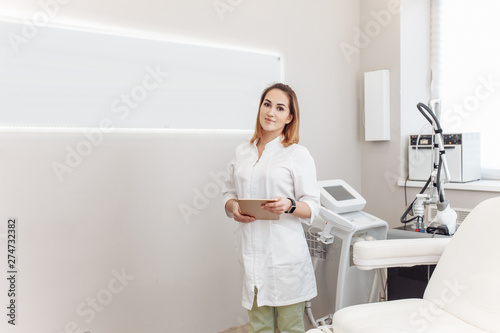 Photo  Beautiful young female master in a beauty salon invites you to modern anti-aging procedures