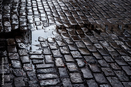 Fotografia, Obraz view of Grungy cobblestone street with puddles, New York City