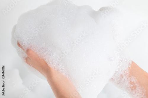 A lot of foam in the hands of a man in the bathroom Fototapet