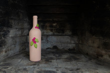 A Hand-painted Empty Wine Bottle With Individual Decorative Design Of Flowers Set In A Blackened Stone Fireplace With Copy Space