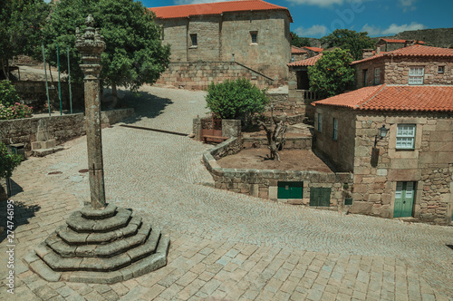 Stone houses and chapel encircling a square with pillory Wallpaper Mural