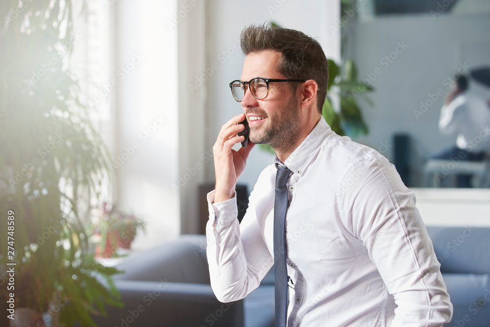 Fototapeta Businessman making a call while sitting in the office