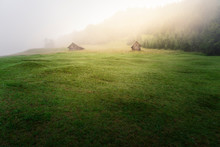 Two Cabins In An Area Of ​​the Bavarian Alps During A Misty Summer Dawn