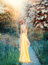 Humanization Of Sunlight, Slim Girl In Magnificent Gentle Seductive Yellow Dress Of The Renaissance Epoch, Lady With Long Blond Hair, Queen Of Summer Awakens Plants After Long Cold With Warmth.