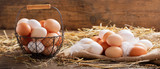 Fototapeta Coffie - basket of colorful fresh eggs on wooden table