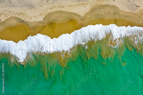 Photo  Drone aerial of waves mixing with sand off of the Southern California coast