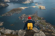 Man sitting on cliff edge alone enjoying aerial view backpacking lifestyle travel adventure outdoor vacations in Norway top of Reinebringen mountain.