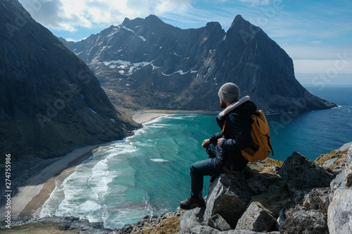 Obraz Man sitting on cliff edge alone enjoying aerial view backpacking lifestyle travel adventure outdoor vacations in Norway top of Reinebringen mountain. - fototapety do salonu