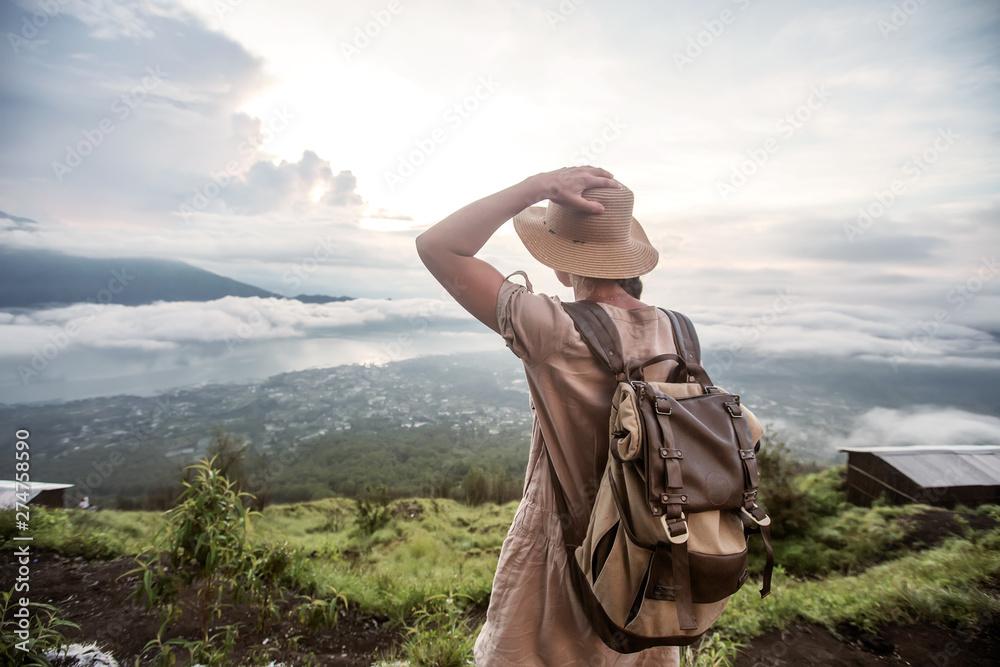 Fototapety, obrazy: Woman enjoying sunrise from a top of mountain Batur, Bali, Indonesia.