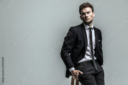 Obraz Portrait of young and handsome model in a classic black and white style clothing. Studio shot. Copy space. - fototapety do salonu