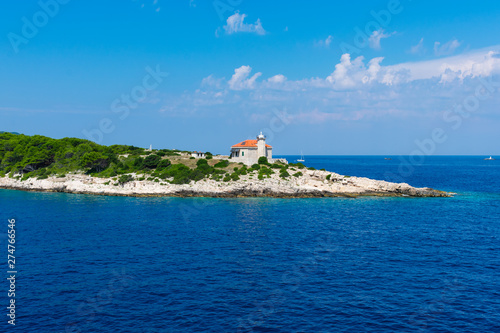 Poster Nouvelle Zélande Seascape view of a small lighthouse on a green peninsula at the entrance of city of Vis harbour in Croatia, on a bright summer day