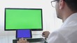 Engineer, Constructor, Designer in Glasses Working on a Personal Computer with a Green Screen on Monitor which has Chroma Key Great for Mockup Template.
