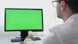 Engineer, Constructor, Designer in Glasses Working on a Personal Computer with a Green Screen on Monitor which has Chroma Key Great for Mockup Template. Designing using CAD Software. Freelance Work