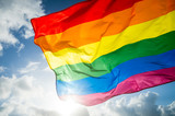 Fototapeta Tęcza - Close-up of gay pride rainbow flag fluttering backlit in bright sunny sky
