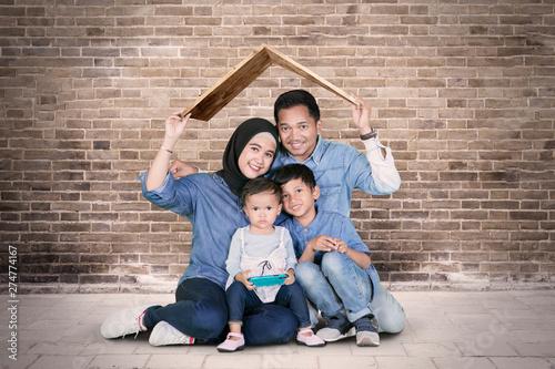 Fotografía  Smiling Muslim family sits under a roof symbol