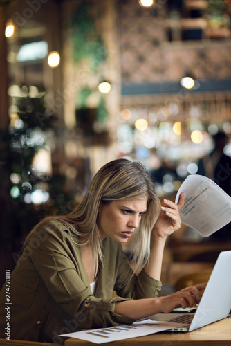 Fotomural  Young worried businesswoman reading a problematic e-mail while going through rep