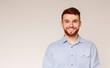 Portrait of smiling millenial guy on beige background