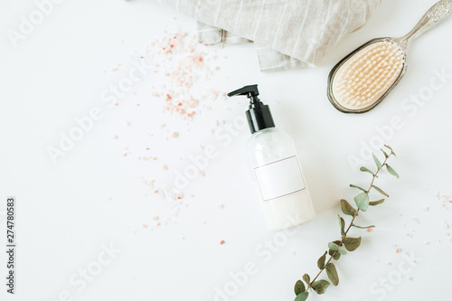 Healthcare spa concept with copy space liquid soap bottle, eucalyptus, hairbrush on white background. Flat lay, top view beauty lifestyle composition.