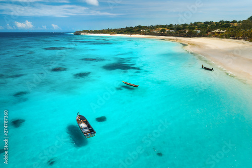 Foto auf Leinwand Turkis Aerial view of boats on tropical sea coast with sandy beach at sunny day. Summer holiday on Indian Ocean, Zanzibar, Africa. Landscape with boat, palm trees, transparent blue water, sky. Top view