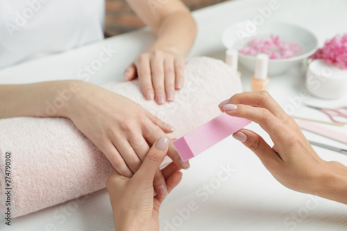 Montage in der Fensternische Maniküre Manicurist polishing client's nails with buffer at table, closeup. Spa treatment