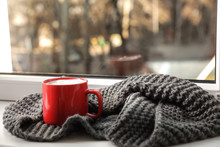 Cup Of Winter Drink And Knitted Scarf On Windowsill. Space For Text